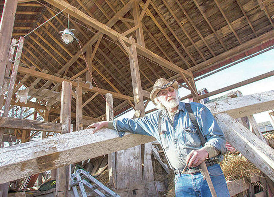 Dan Sutton stands next to a barn beam he has started to remove from a barn in rural Morrison. It is the 95th barn Sutton has dismantled to reclaim the lumber since 1980. Photo: Michael Krabbenhoeft | The Telegraph (AP)