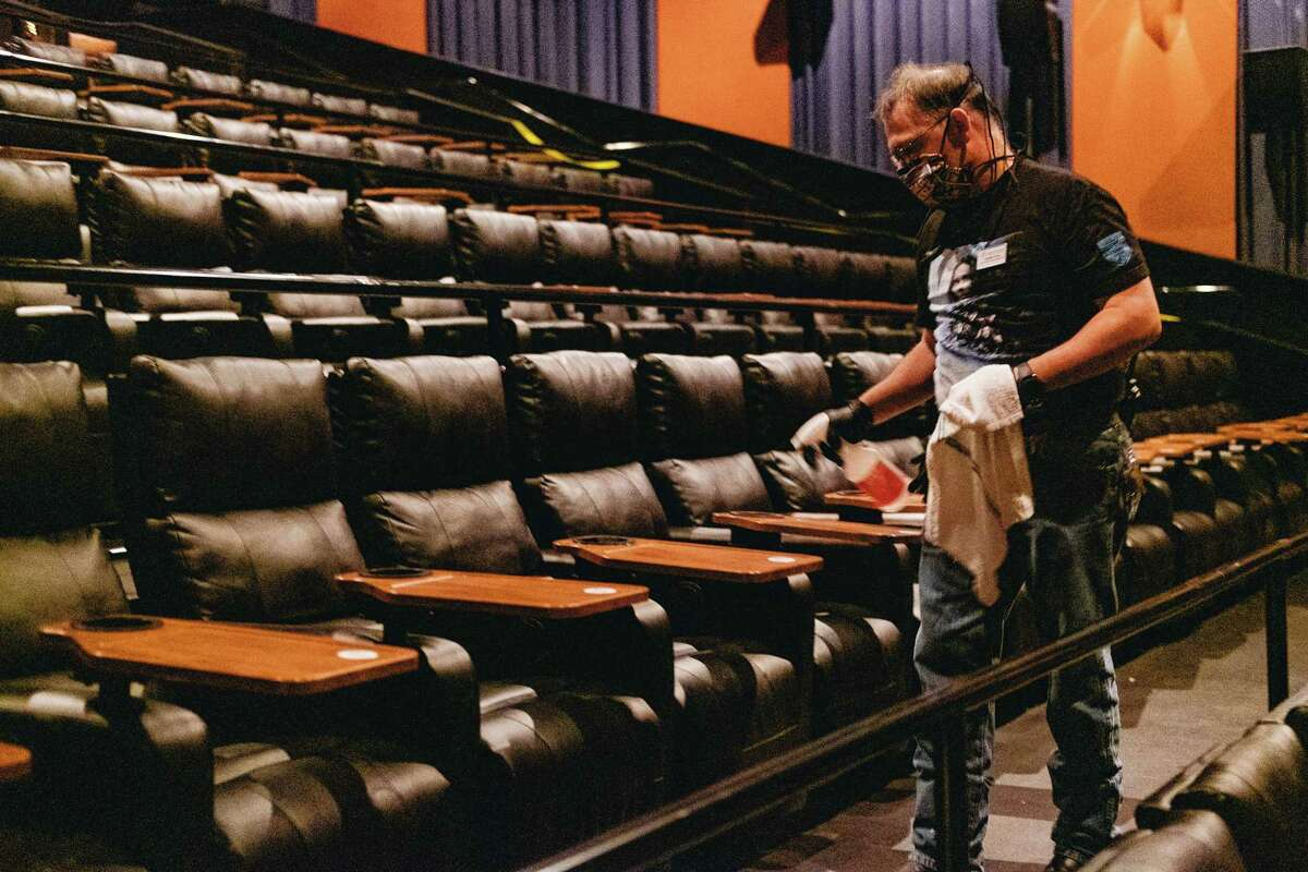 A masked staff member cleans up after a movie at the Palladium Cinema in San Antonio, May 2, 2020. A few movie theaters in Texas opened on Saturday, early experiments in back-to-normal living after a long coronavirus lockdown. (Christopher Lee/The New York Times)