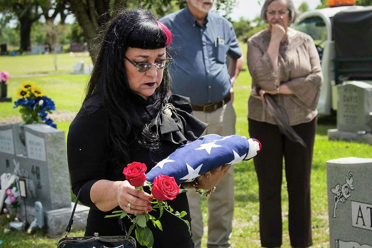 Sue Ellen Davis drops flowers into the grave of her father, Marine veteran James Virgil Davis, during his funeral on Saturday, May 2, 2020 at Angleton Cemetery in Angleton. Davis died April 27 at age 89 in an assisted living facility, after surviving COVID-19. Sue Ellen Davis had tried for weeks to move him into her Angleton home. He had Alzheimer's and was on hospice. She was there for a daily window visit when he passed.