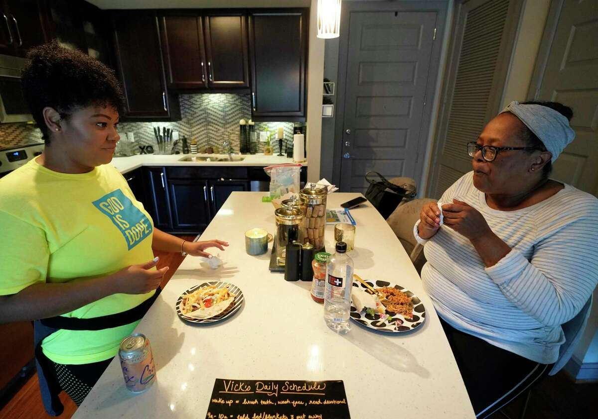 G'Nai Blakemore, left, and her aunt Vicki Brown, right, have dinner in her one bedroom apartment where she has her aunt staying with her amid the Covid-19 pandemic Thursday, April 30, 2020, in Houston. Vicki was living at a personal care home and G'Nai worried her aunt would get sick.