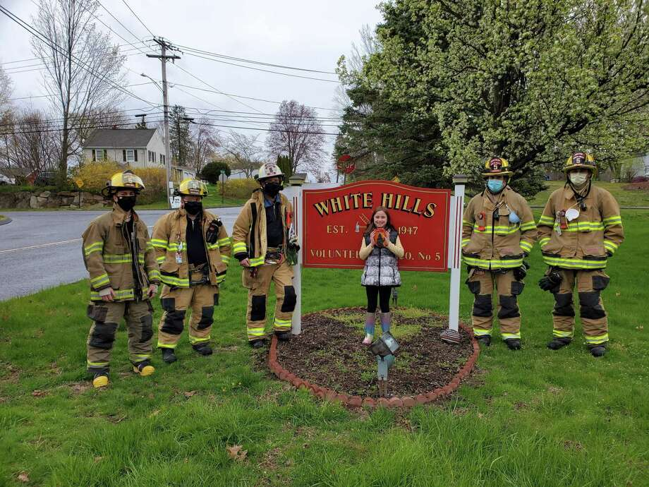 Gia Camarota displays the rock her mother painted in support of White Hills Fire Company. Photo: Contributed Photo / Connecticut Post