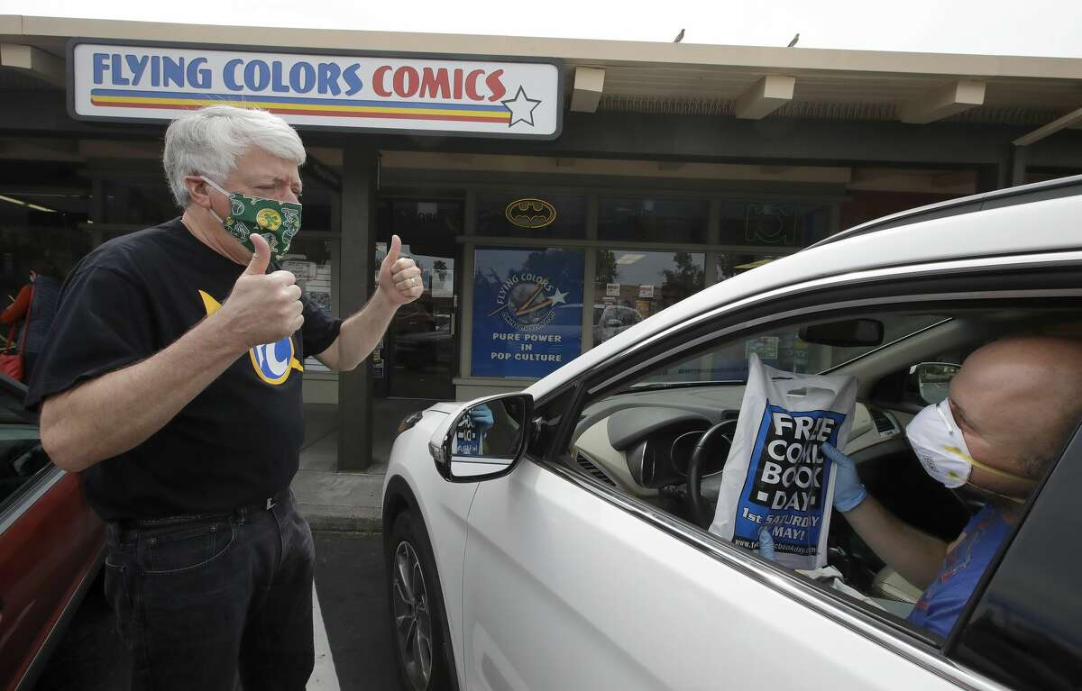 In this Wednesday, April 29, 2020 photo, Joe Feld, owner of Flying Color Comics, left, gestures after making a curbside delivery of comic books to Elias Panos in Concord, Calif.
