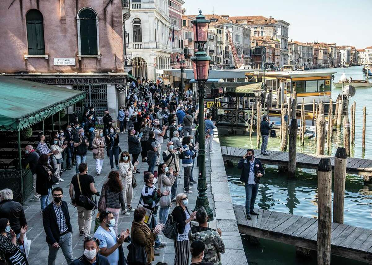People gather near the Rialto Bridge in Venice on May 4 in a demonstration seeking the loosening of restrictions on commercial activities, including on restaurants and bars, that were imposed to slow the spread of the coronavirus.