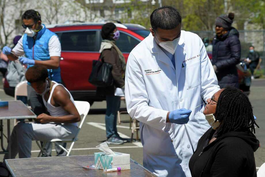 Dr. Fawad Hameedi of DOCS Urgent Care Stamford administers a COVID-19 nasal swab test on Lakeisha Thompson, 34, of Stamford at a walk up testing site for the Coronavirus at AME Bethel Church in Stamford, Connecticut on May 2, 2020. Over 200 tests were perform by medical professinals for residents of Stamford's Westside. Photo: Matthew Brown / Hearst Connecticut Media / Stamford Advocate