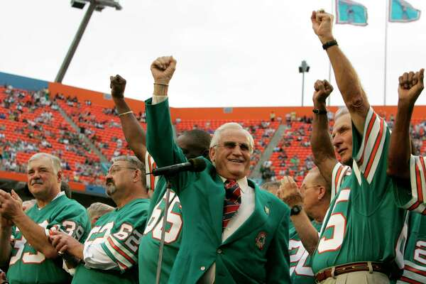 """Former Miami Dolphins coach Don Shula, center, waves with former players from the 1972 unbeaten team during a ceremony at an NFL football game against the Baltimore Ravens at Dolphin Stadium in Miami on Sunday, Dec. 16, 2007. From left are running back Larry Csonka (39), center Jim Langer (62) and linebacker Nick Buoniconti, right. New England Patriots coach Bill Belichick remembers the 1972 Dolphins as an """"awesome team."""" He was """"a big fan"""" of Shula. Now Belichick's Patriots are trying to match those Dolphins by becoming the second NFL team to have an undefeated season."""
