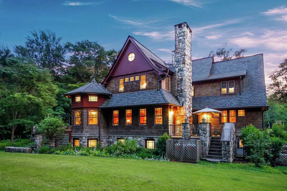 The natural wood-colored colonial house at 4 Tanglewood Lane is within easy walking distance of Earthplace The Nature Discovery Center and the Lillian Wadsworth Arboretum.