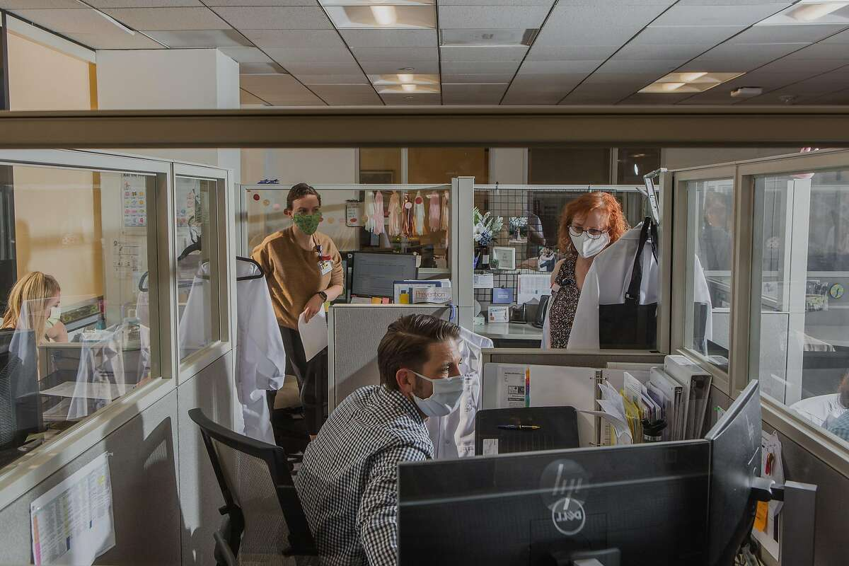 Workers at the office of Infection Prevention at University of California Irvine where protective barriers separate cubicles, Orange, Calif., April 27, 2020. As businesses contemplate the return of workers to their desks, many are considering large and small changes to the modern workplace culture and trappings. (Alex Welsh/The New York Times)