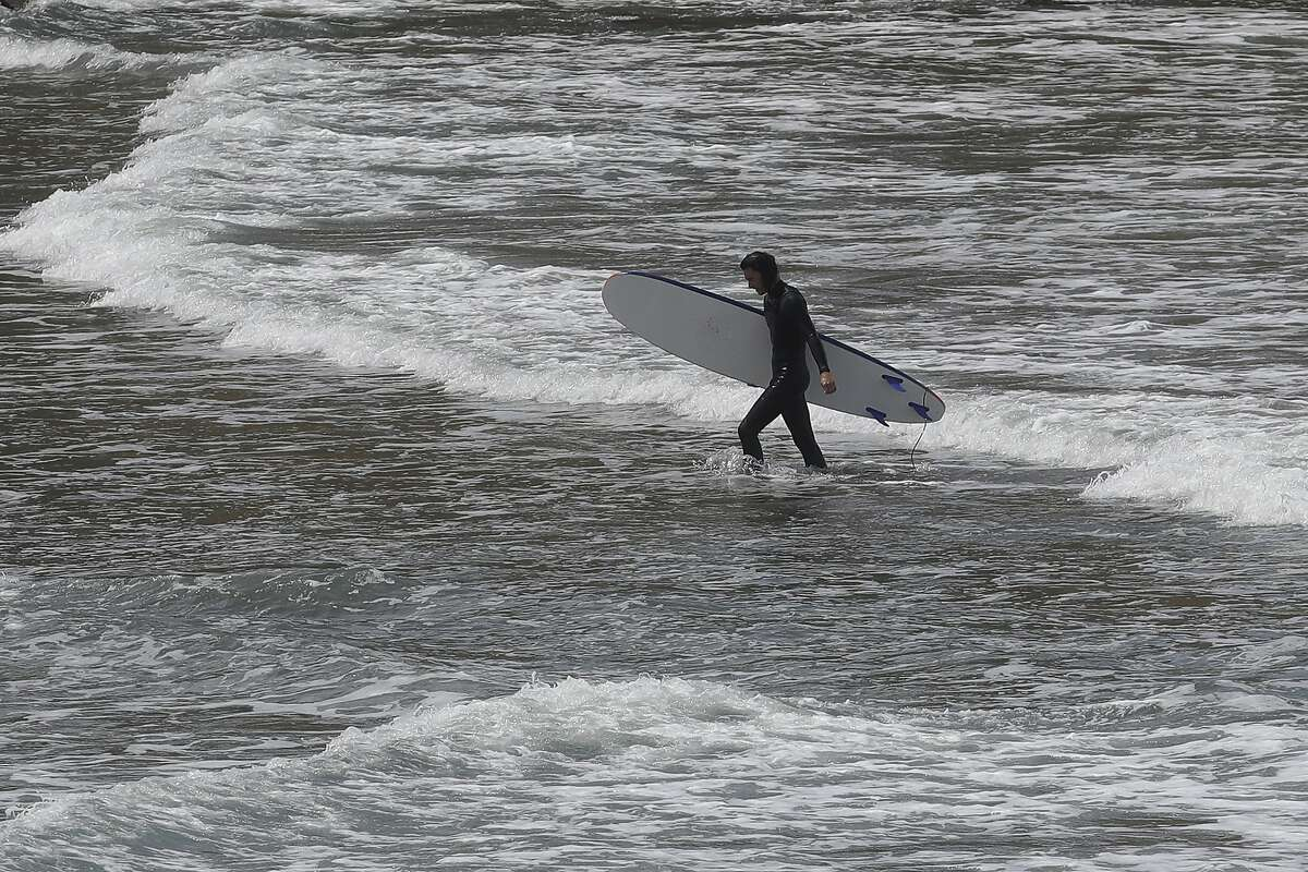 A surfer leaves the water at Rockaway Beach in Pacifica, Calif., Saturday, May 2, 2020. A week after Californians weary of stay-at-home orders packed beaches, authorities pleaded for weekend visitors to follow social distancing rules: no bunching, keep walking or swimming, and leave the umbrellas at home. (AP Photo/Jeff Chiu)