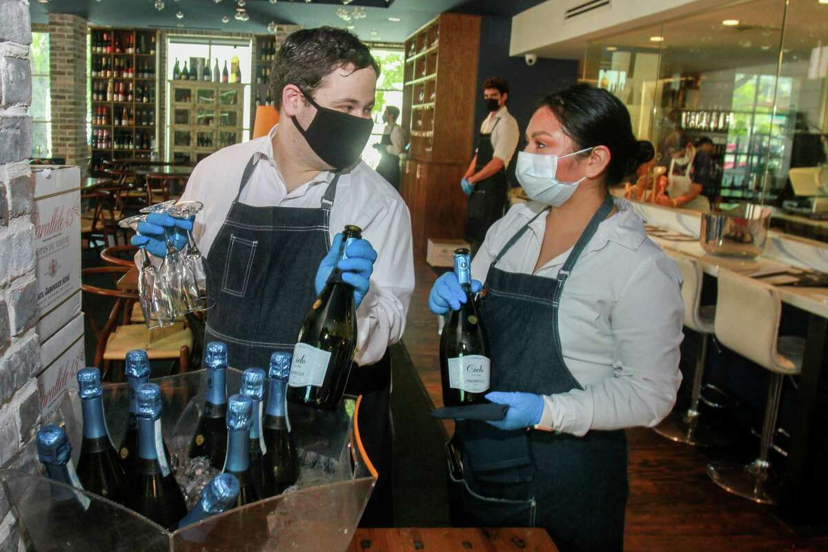 Waiters at a'Bouzy in Houston during the business' reopening on May 1, 2020.
