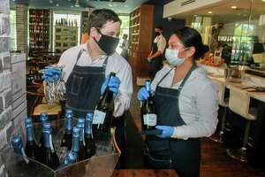 Waiters Trent Hart and Isabel Hernandez at a'Bouzy in Houston during their reopening on May 1, 2020.