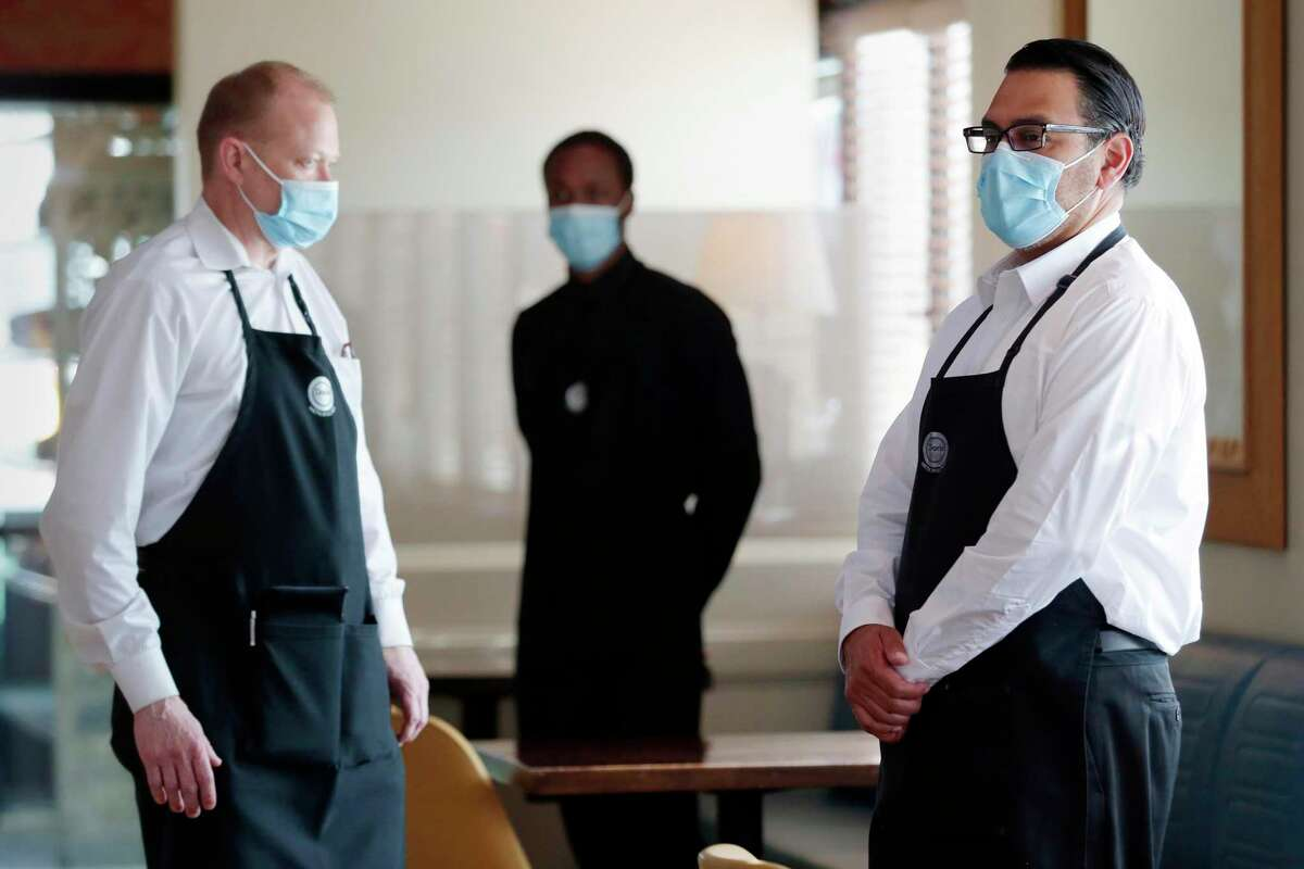Serving staff, from left, Lee Collins, Michael Cormier and Derik Duran wait in their face masks for customers to start arriving during the first night of reopening of the Doris Metropolitan restaurant Friday, May 1, 2020 in Houston, TX, after the state loosened social distancing restrictions.