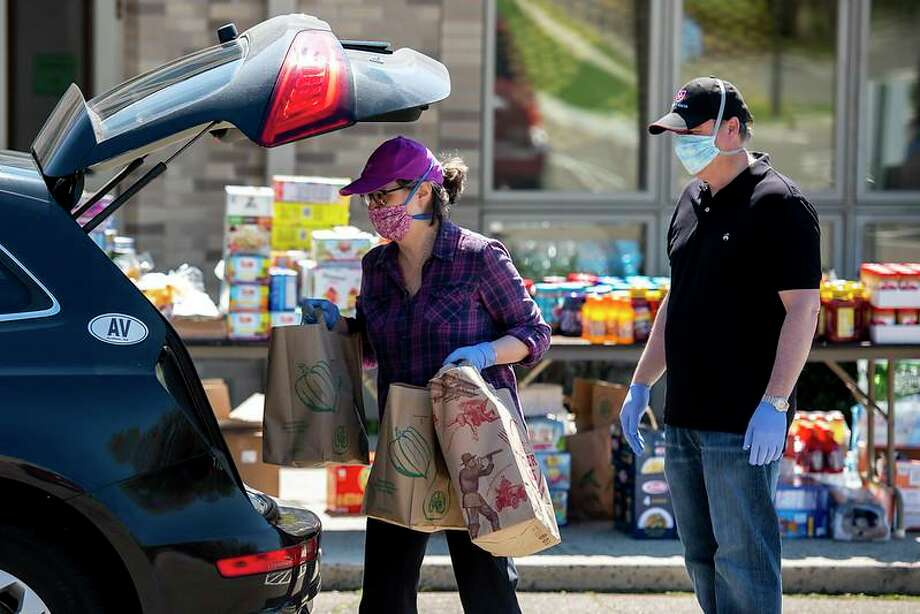 The Parish of St. Catherine of Siena held a Drive Through Food Drive to support local food pantries on May 2. More than 150 cars came through and more than $3,000 in cash donations and food donations overflowed from nearly 100 feet of tables. Photo: Contributed Photos / COPYWRIGT