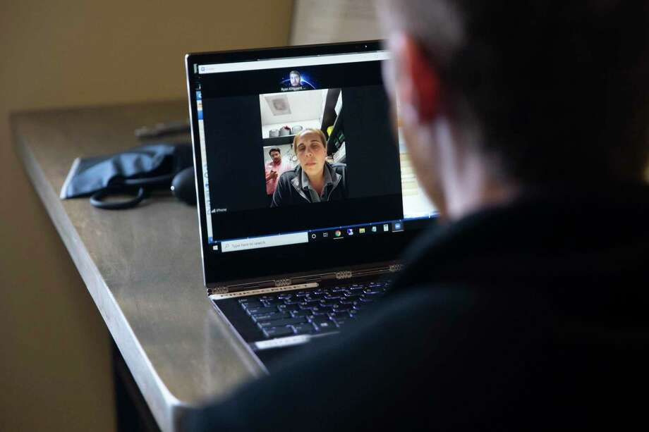 Dr. Ryan Klitgaard, right, speaks with a patient during a telemedicine appointment online at the MaxHealth Family, Internal & Sports Medicine clinic in Colleyville, Texas, on March 20, 2020. (Lynda M. Gonzalez/Dallas Morning News/TNS) Photo: Lynda M. Gonzalez, FILE / TNS / Dallas Morning News