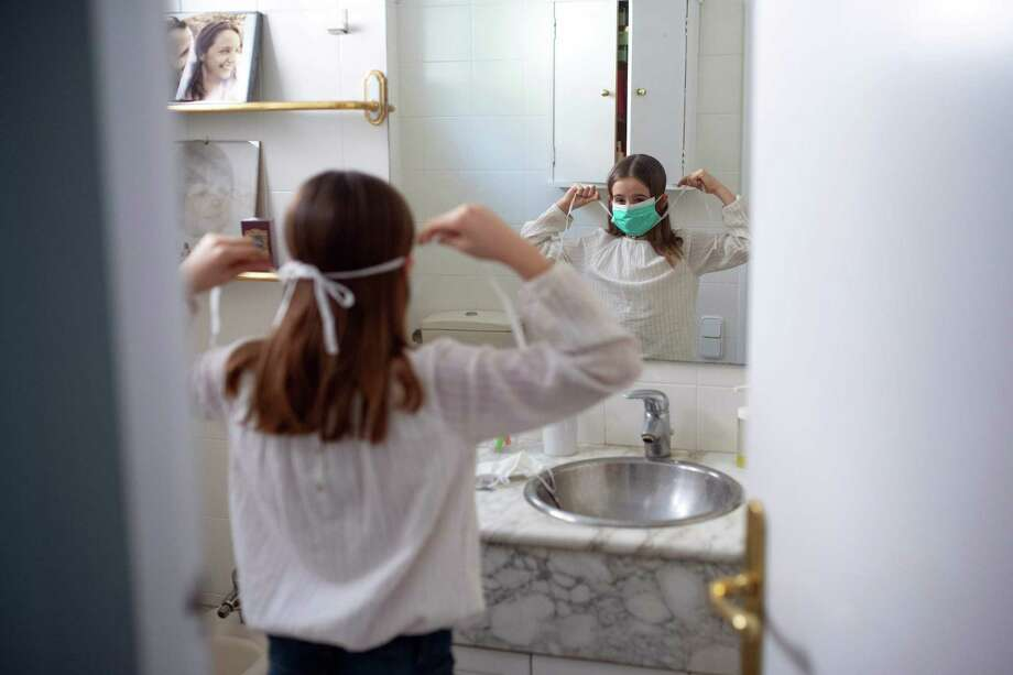 Ines, 11, puts on her face mask prior to going out with her family on April 26, 2020, in Barcelona, during a national lockdown to prevent the spread of the COVID-19 disease. Photo: Josep Lago / Getty Images / AFP or licensors