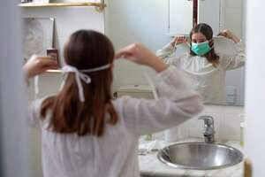 Ines, 11, puts on her face mask prior to going out with her family on April 26, 2020, in Barcelona, during a national lockdown to prevent the spread of the COVID-19 disease.