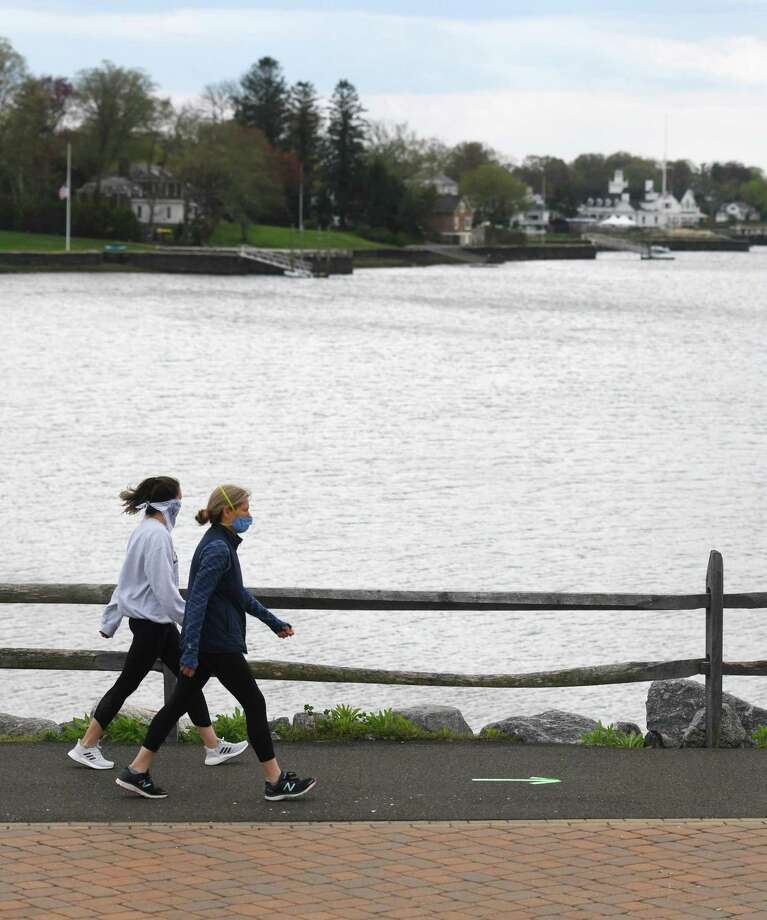 "Stamford residents Molly Clisham, left, and Dawn Clisham walk in the proper direction, as indicated by an arrow on the path, at the newly re-opened Cos Cob Park in the Cos Cob section of Greenwich, Conn. Monday, May 4, 2020. Greenwich loosened some of its coronavirus restrictions Monday by re-opening Griffith E. Harris Golf Course and Cos Cob Park. ""The Griff"" is open with mandatory social distancing regulations, required masks, and a one person per cart rule while Cos Cob Park is open also with mandatory social distancing regulations and required masks. Photo: Tyler Sizemore / Hearst Connecticut Media / Greenwich Time"