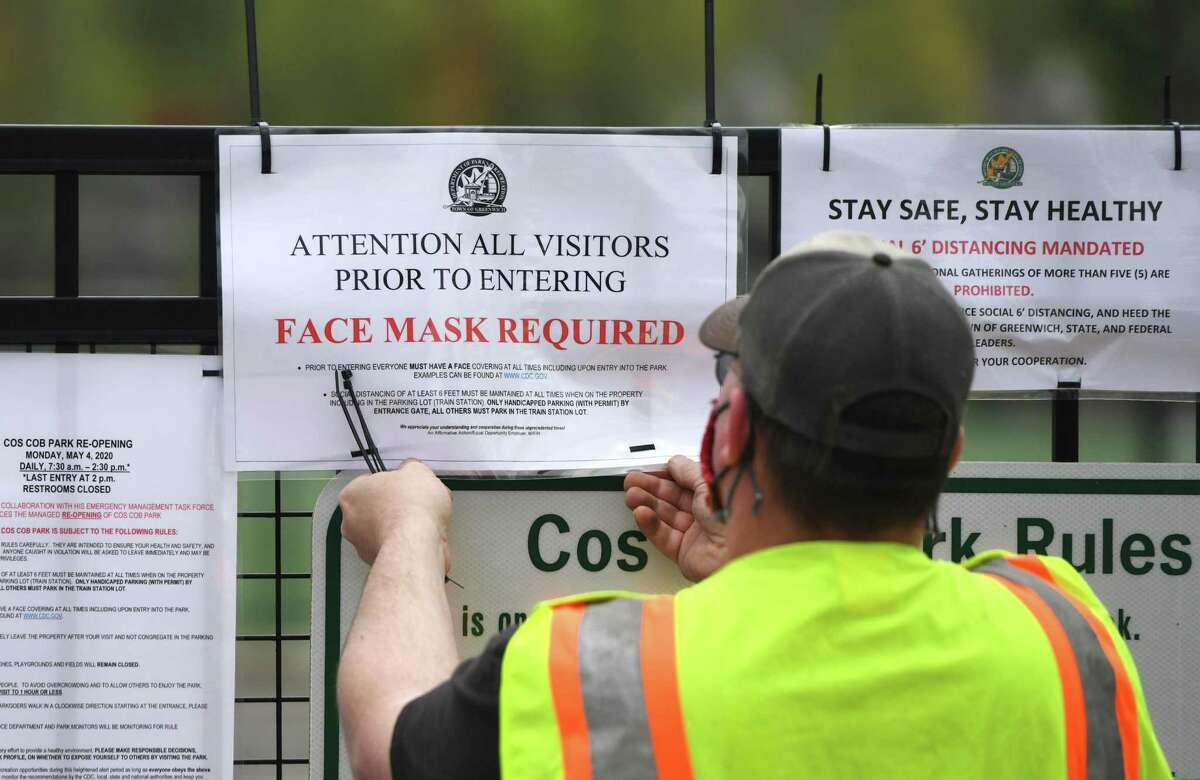 A town employee posts a sign requiring face masks at the newly re-opened Cos Cob Park in the Cos Cob section of Greenwich, Conn. Monday, May 4, 2020. Greenwich loosened some of its coronavirus restrictions Monday by re-opening Griffith E. Harris Golf Course and Cos Cob Park.