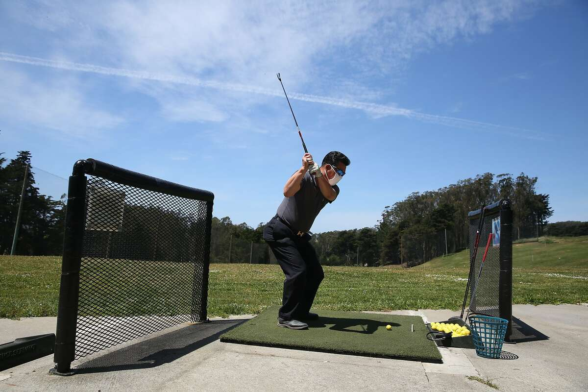 Song Hong of San Francisco hits golf balls on the driving range where golfers kept one empty space between them at the Presidio Golf Course on Monday, May 4, 2020 in San Francisco, Calif.