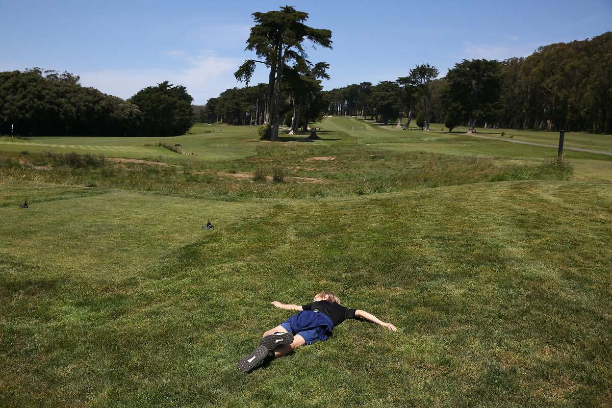 Luca, 11, of San Francisco lies in the grass at the Presidio Golf Course while enjoying some time outdoors with his mother and brother on Monday, May 4, 2020 in San Francisco, Calif.