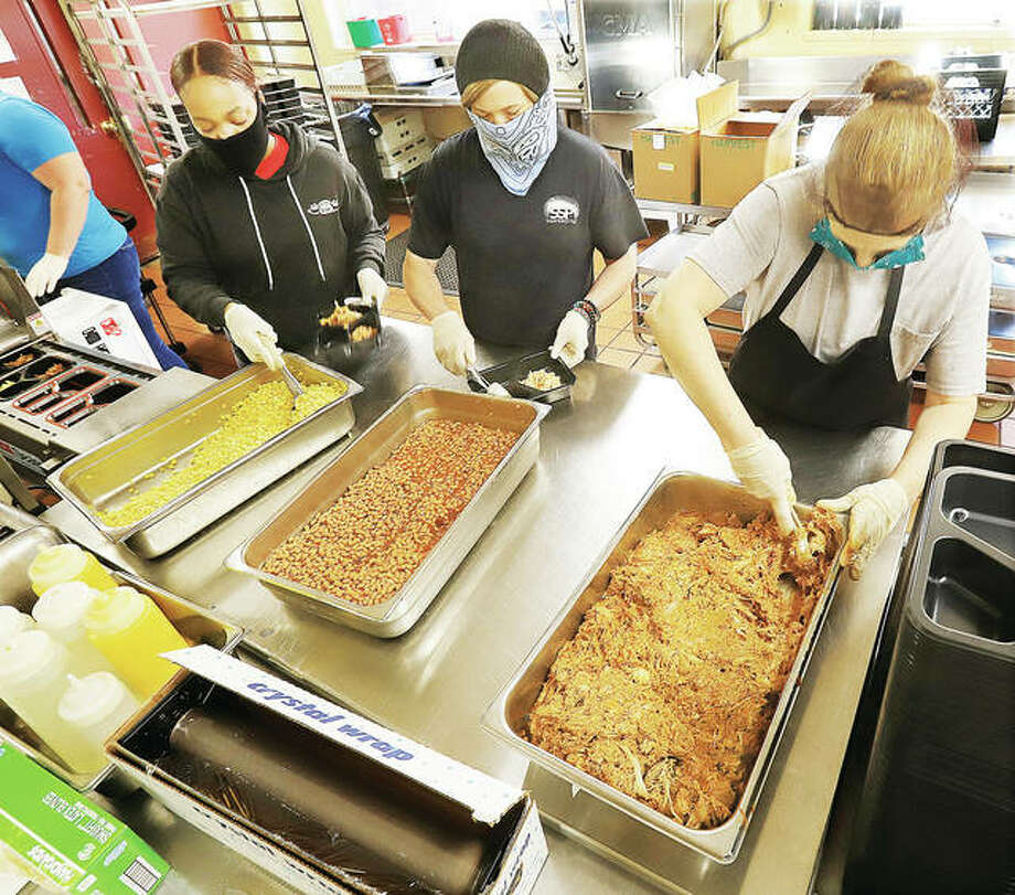 Workers in the kitchen at Alton's Senior Services Plus dish up food trays for the Meals on Wheels program early Monday morning. The food is sealed in trays by a machine, much like a traditional TV dinner.
