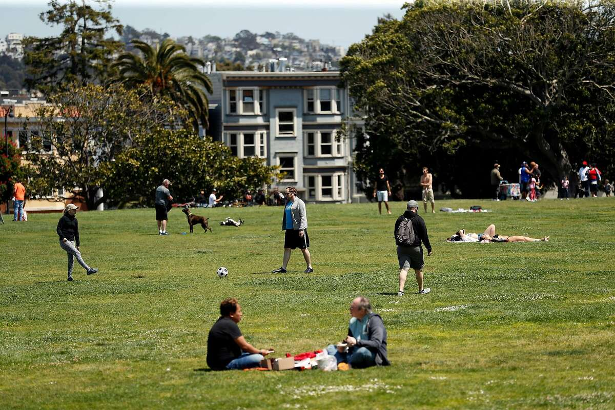 People practice social distancing while spending time at Dolores Park in San Francisco, Calif., on Monday, May 4, 2020.