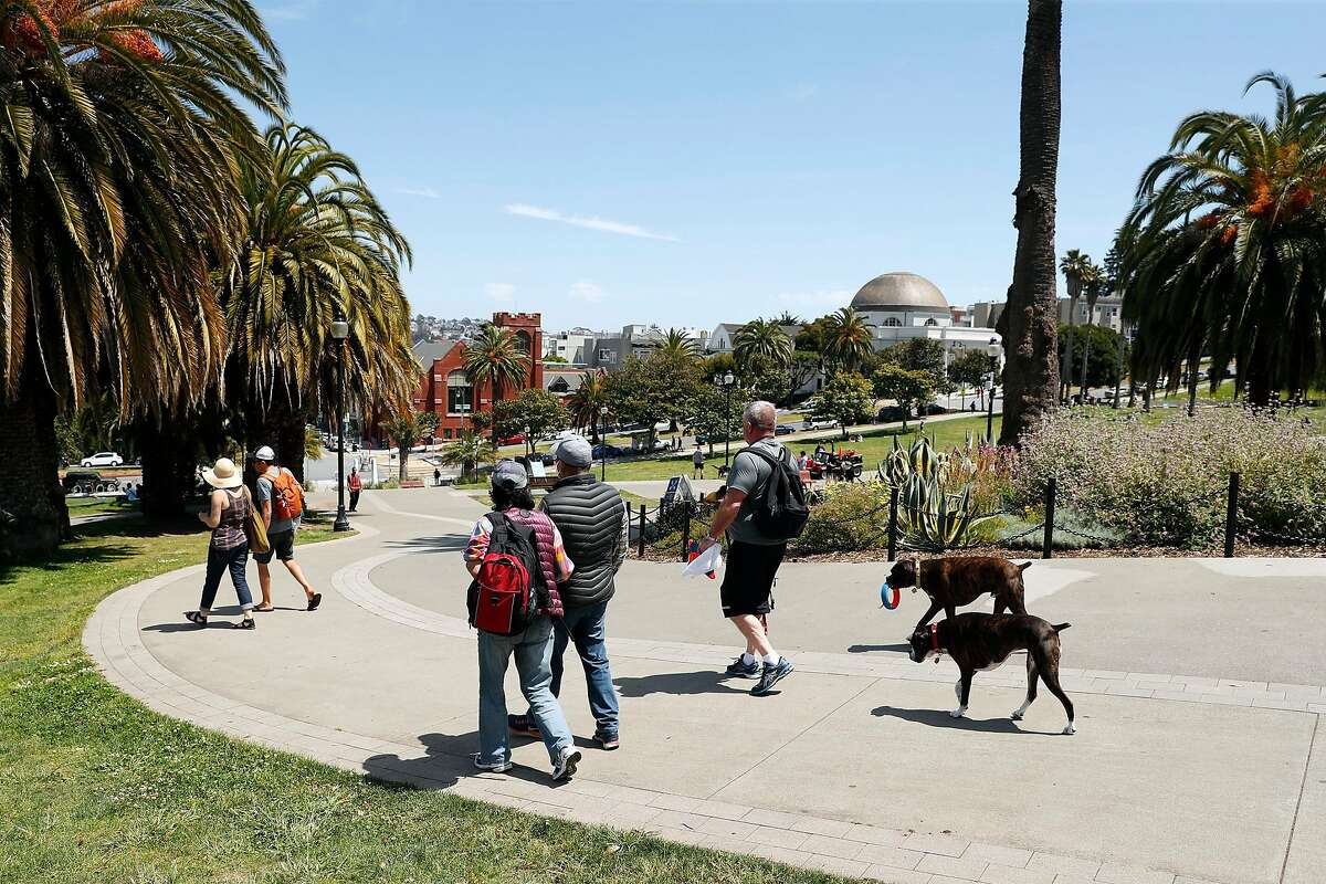 People and dogs arrive at Dolores Park in San Francisco, Calif., on Monday, May 4, 2020.