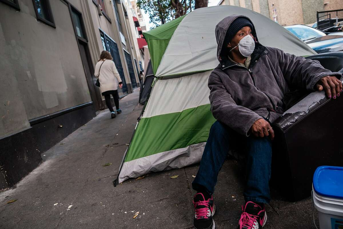 Joanie Stinson sits on the sidewalk near a row of tents in the Tenderloin in San Francisco, Calif. on Friday April 10, 2020.