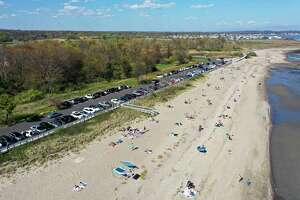 Groups of people gather Sunday at beaches in Milford, including Silver Sands State Park, which was closed to new visitors by the afternoon when the parking lot reached capacity.