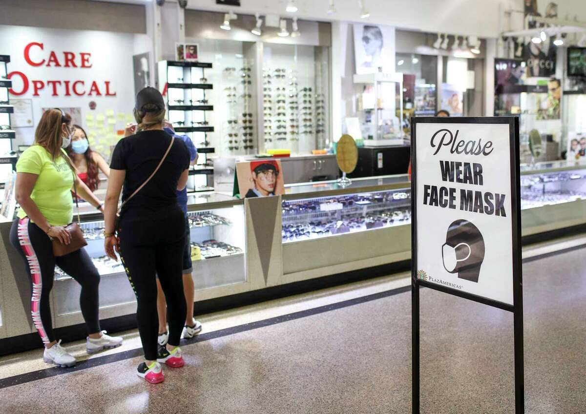 A sign directs people to wear a mask, Friday, May 1, 2020, at PlazAmericas mall in Houston. Retailers are trying to figure out how to safely open after Gov. Greg Abbott allowed Texas businesses to reopen May 1 at reduced capacity, despite the COVID-19 pandemic.