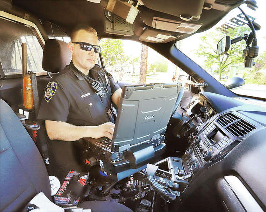 Alton Police Officer John Wimmersberg works at the data terminal inside his patrol car while on duty in Alton. Photo: John Badman | The Telegraph