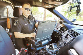 Alton Police Officer John Wimmersberg works at the data terminal inside his patrol car while on duty in Alton.