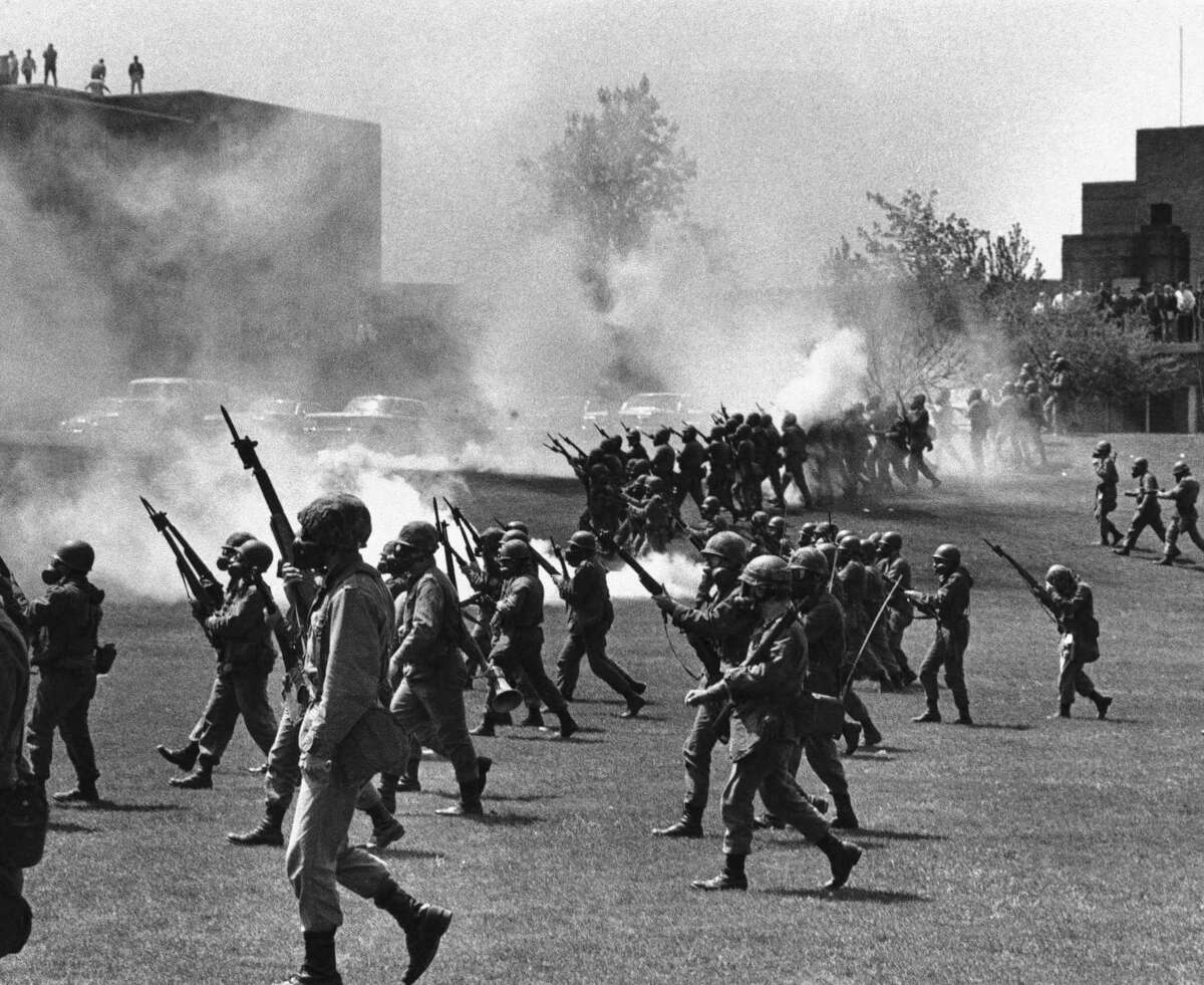 FILE - In a May 4, 1970 file photo, Ohio National Guard moves in on rioting students at Kent State University in Kent, Ohio. Four persons were killed and eleven wounded when National Guardsmen opened fire. The U.S. Justice Department, citing