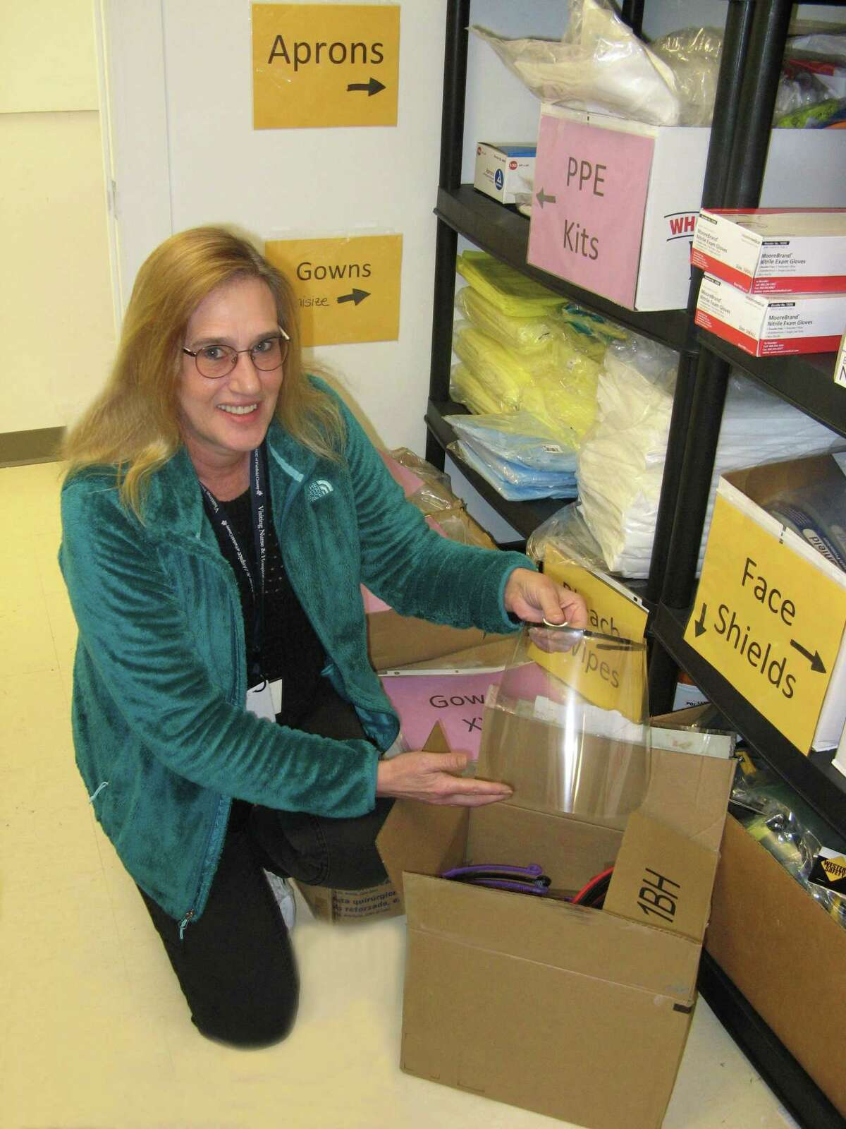 Ellen Dobson opens a box of face shields donated to Visiting Nurse & Hospice of Fairfield County by the Wilton Health Department.
