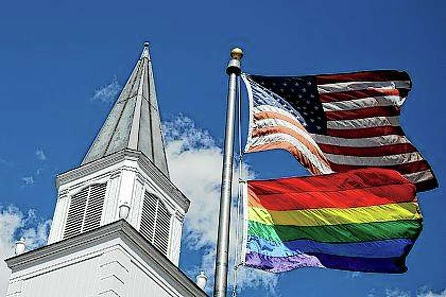 A gay pride rainbow flag flies April 19, 2019, along with the U.S. flag in front of Asbury United Methodist Church in Prairie Village, Kansas. The United Methodist Church was supposed to be meeting this week to decide what to do about a wide split in the denonimation, but those plans are on hold as the coronavirus pandemic continues. Photo: Charlie Riedel | Associated Press