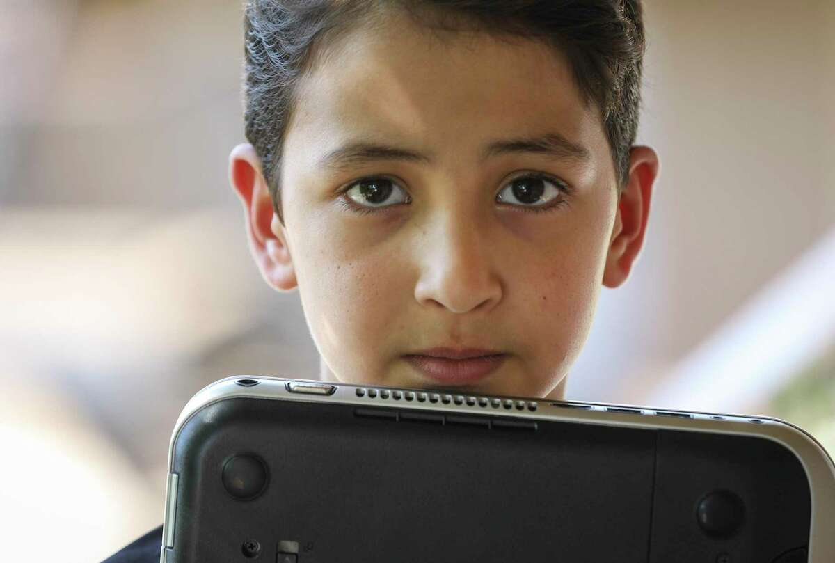 Yousuf Durrani, 8, holds his laptop Friday, April 24, 2020, at their apartment in Houston. Durrani, his brother and their two sisters share a laptop to do their schoolwork.