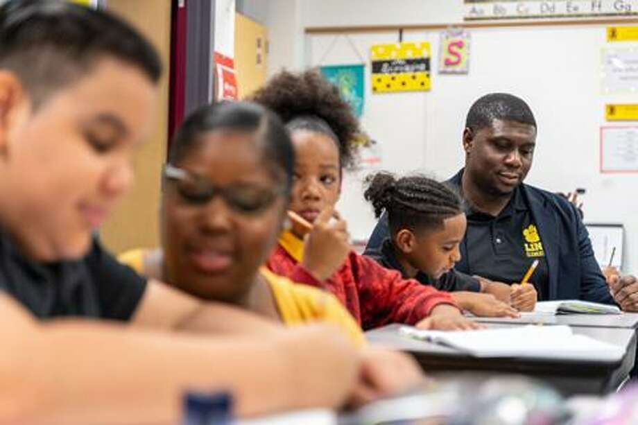 Justin Jones sits with students in a classroom at Link Elementary School. Photo: Courtesy Of Spring ISD