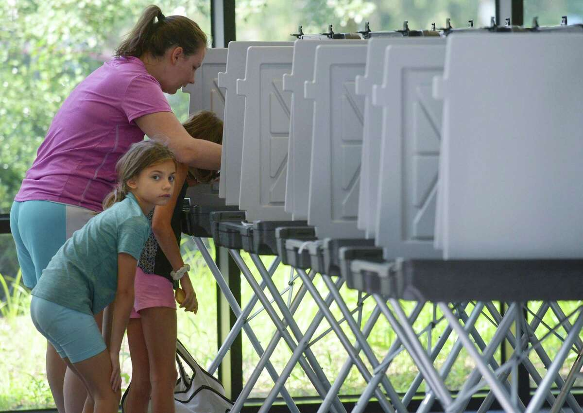 Jennifer Carvajal casts her ballot in a primary accompanied by her daughters on Tuesday, August 14, 2018, at Wilton High School.