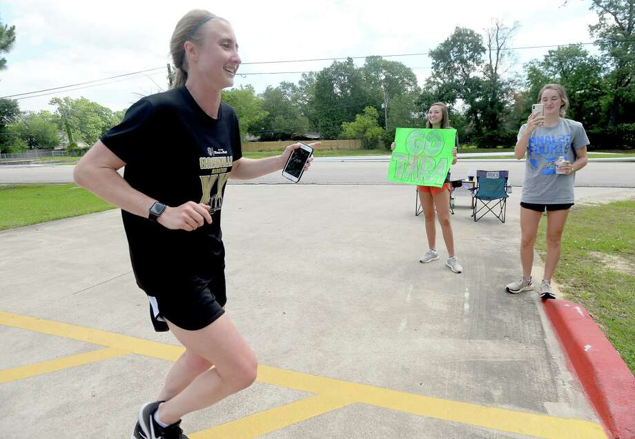 Kelly soccer players Abigail Nickum (left) and Julia Phelan wave and cheer as Tara Austin makes a pass by their donation and support station, one of several spread along the 14-mile route of her run to raise money for charitable service organizations. Austin, a soccer coach at Monsignor Kelly Catholic High School, was set to run the Boston Marathon before the event was postponed due to the coronavirus. In its stead, she chose to run for charity, which began and ended at the Folsom Hike & Bike Trail Monday morning. In addition to accepting donations at the route stations, she started a GoFundMe, which will remain open for donations throughout the week. Photo taken Monday, May 4, 2020 Kim Brent/The Enterprise Photo: Kim Brent, The Enterprise / BEN