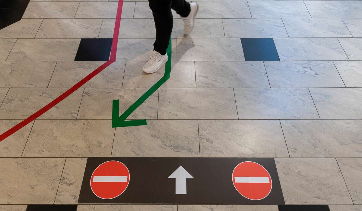 The arrows aim to direct traffic, keeping people moving in one direction to prevent inadvertent contact in walkways.