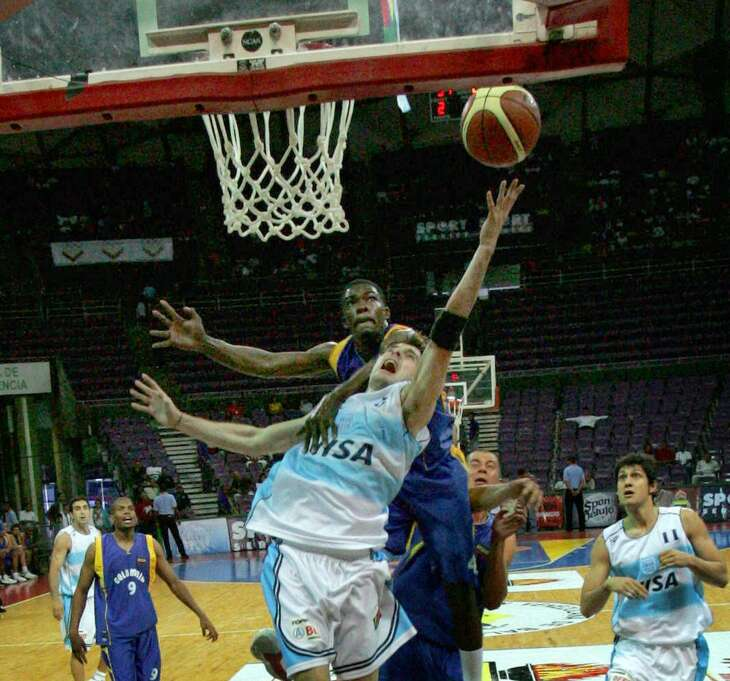 Colombia's Alvaro Tehran attempts to block a shot by Argentina's Nicolas Gianella in the South American Basketball Cup on July 12, 2006 in Caracas, Venezuela.