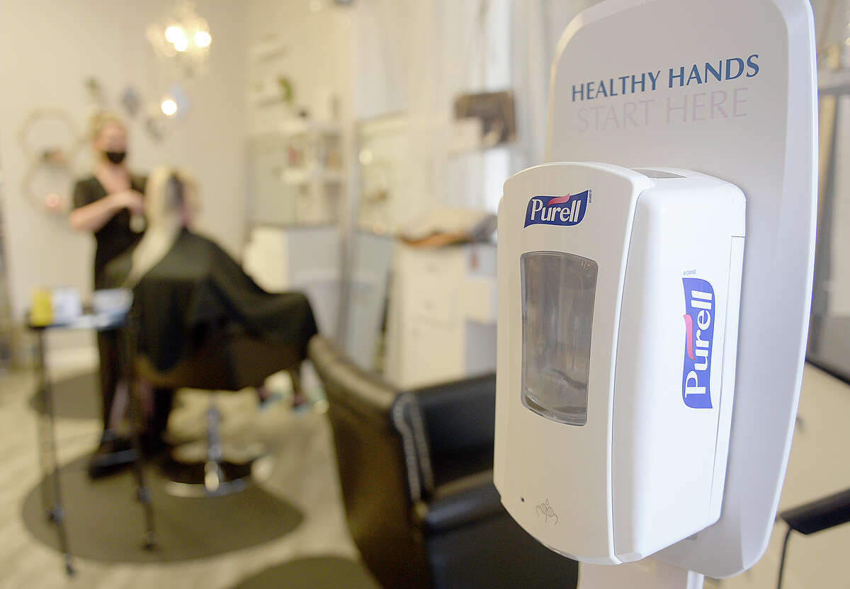 A hand sanitizer dispenser placed near the entrance of Hairendipity Salon in Vacaville, California on Thursday April 30, 2020. Salon owner, Lia Rivera has re-opened her downtown after being shut down for the past month-and-a-half due to the shelter-at-home order.