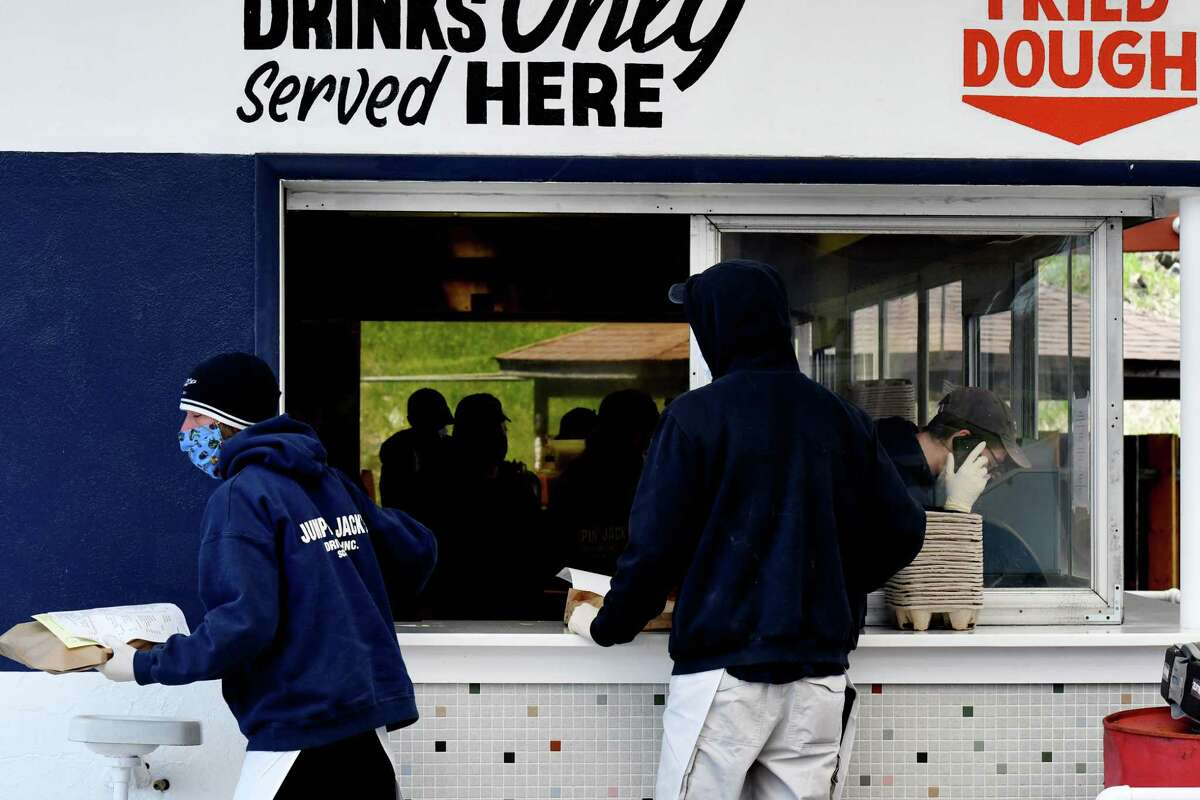 Orders are delivered to waiting customers during the opening day for Jumpin' Jack's Drive-in on Tuesday, May, 5, 2020, in Albany, N.Y. The famed local eatery is currently only taking orders by phone for curbside pickup during the coronavirus lockdown. Customers are asked to remain in their cars, and bathrooms are closed. They're open 11a.m. - 8.p.m. daily, according to their website. (Will Waldron/Times Union)