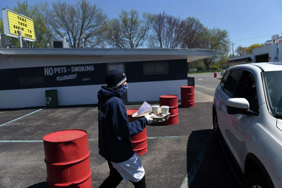 An order is delivered to a customer during the opening day for Jumpin' Jack's Drive-in on Tuesday, May, 5, 2020, in Albany, N.Y. The famed local eatery is currently only taking orders by phone for curbside pickup during the coronavirus lockdown. Customers are asked to remain in their cars, and bathrooms are closed. They're open 11a.m. - 8.p.m. daily, according to their website. (Will Waldron/Times Union)