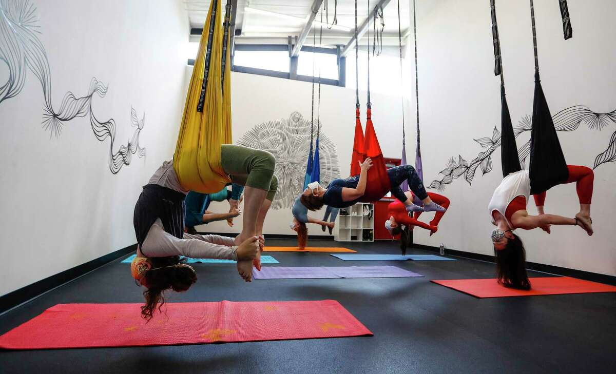 A group of clients, spaced six feet apart, hang from their baskets in a studio at Republic Aerial Yoga, in Houston, Saturday, May 2, 2020. Republic Aerial Yoga owner Amanda Field has been struggling since she had to shut her studio down in the Arts District in 1st Ward. She was making profit in January, but everything has changed in the last month. She has picked up a second job, she has turned to giving away free livestream yoga classes on Instagram and she is still worried about her $4,000 a month rent.