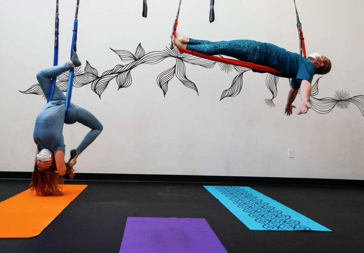 Chris Regan and his daughter Madelynn, 15, hang from their baskets at Republic Aerial Yoga, in Houston, Saturday, May 2, 2020. Republic Aerial Yoga owner Amanda Field has been struggling since she had to shut her studio down in the Arts District in 1st Ward. She was making profit in January, but everything has changed in the last month. She has picked up a second job, she has turned to giving away free livestream yoga classes on Instagram and she is still worried about her $4,000 a month rent.