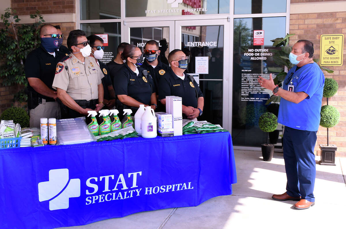 STAT Specialty Hospital-Laredo North CEO Carlos Diaz, right, addresses Webb County Constable Rudy Rodriguez and some of his deputies, Monday, May 4, 2020, after the law enforcement office was presented with items to stay safe during the COVID-19 pandemic.