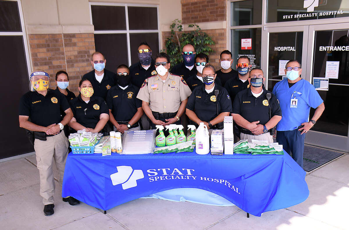 STAT Specialty Hospital-Laredo North CEO Carlos Diaz, right, poses Webb County Constable Rudy Rodriguez and some of his deputies, Monday, May 4, 2020, after the law enforcement office was presented with items to stay safe during the COVID-19 pandemic.