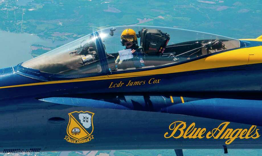 "Lt. Cmdr. Jim Cox, the U.S. Navy Flight Demonstration Squadron, the Blue Angels, slot pilot, displays an ""American Strong"" sign while transiting to Baltimore as part of Operation American Strong on May 2, 2020. ""America Strong,"" to be held in various US cities, recognizes healthcare workers, first responders, military, and other essential personnel on the front lines fighting the COVID-19 pandemic, according to the US Defense Department. The Blue Angels are scheduled to fly over Dallas, Houston and New Orleans mid-day on Wednesday. They are expected to fly over Conroe/The Woodlands from 12:20 to 12:30 p.m. Photo: CHRISTOPHER GORDON, Contributor / US NAVY/AFP Via Getty Images / AFP"