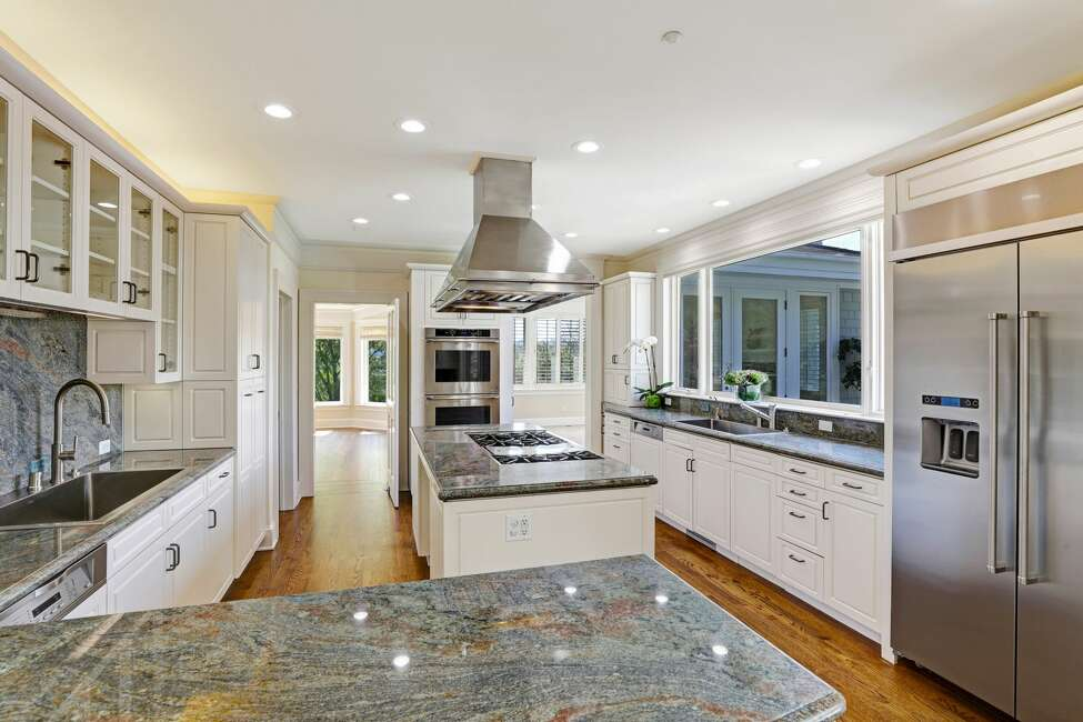The kitchen features a granite center island, a six-burner Wolfe cooktop and stainless appliances.