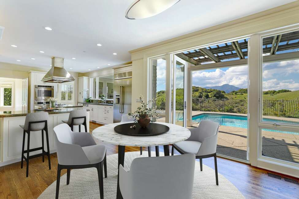 Off the kitchen is a dining nook that opens to the patio and pool. You can view Mt. Tam in the distance.